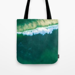 Looking down at beautiful crushing green ocean wave at sunset. Aerial view with copy space. Tote Bag