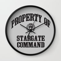 stargate Wall Clocks featuring Property of Stargate Command Athletic Wear Black ink by RockatemanDesigns