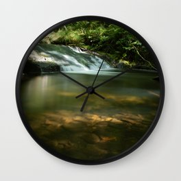 Waterfall in green forest with rocks at sunset Wall Clock