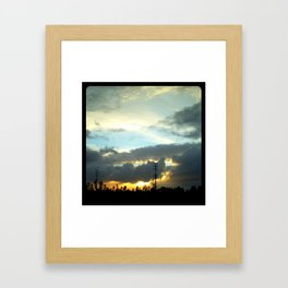 The sun peeking through the clouds. Framed Art Print