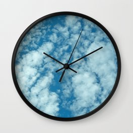 Fluffy clouds in a blue sky Wall Clock