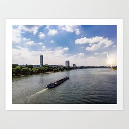 Freight boat through river against cityscape Art Print