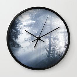 Sun rays shinning through foggy forest Wall Clock