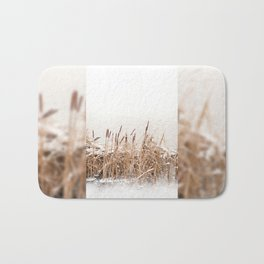 Snow on Typha reeds and frozen water Bath Mat
