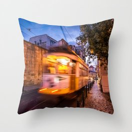 A tram transports tourists through the Alfama District in Lisbon, Portugal at dusk Throw Pillow