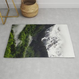 Fog rolling through forest below mountains Rug