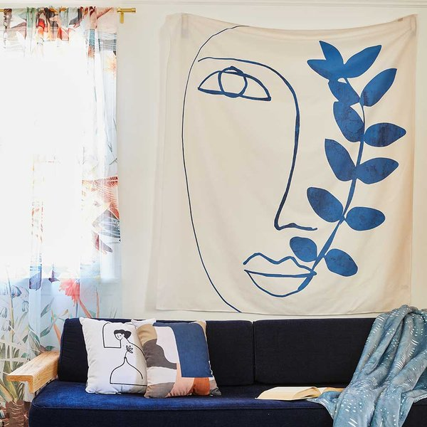 sofa with throw pillows and tapestry