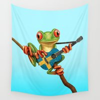 sweden Wall Tapestries featuring Tree Frog Playing Acoustic Guitar with Flag of Sweden by Jeff Bartels