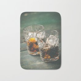 Alcoholic cocktail  with orange peel and ice on wooden table Bath Mat