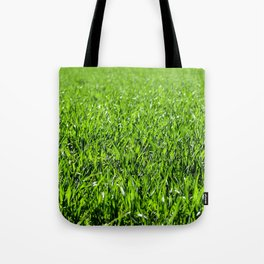 Green grass field in a sunny day Tote Bag