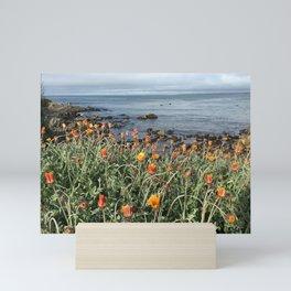 Orange blooms along the Pacific Mini Art Print