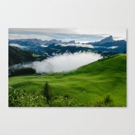 Full green mountain top with clouds beneath Canvas Print