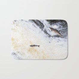 Two salmon leaping up the waterfall Bath Mat
