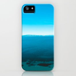 Sea with darken details in the water and mountains in the background iPhone Case