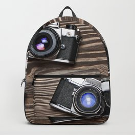 Collection of retro photo cameras on  wood Backpack