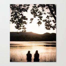 Two girls watching sunset at lake of Banyoles Canvas Print