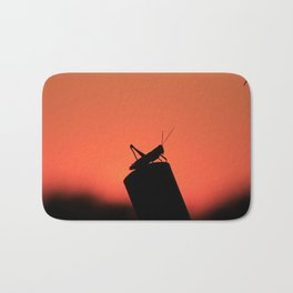 Colorful Kansas Sunset with a Grass Hopper silhouette on a post. Bath Mat