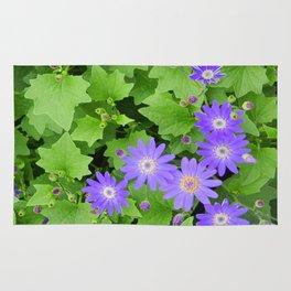 Purple flowers on leafy greens Rug