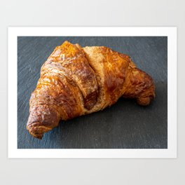 Traditional croissant placed on a dark plate Art Print