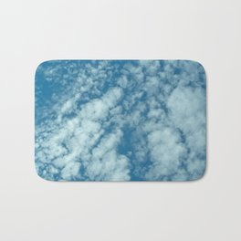 Fluffy clouds in a blue sky Bath Mat
