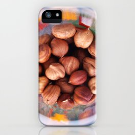 Purified hazelnut in a transparent glass with colored patterns, top view iPhone Case