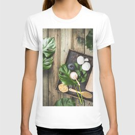 flat lay layout with monstera leaves and cosmetic care products T-shirt