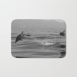 Black and white dolphin race in the ocean Bath Mat