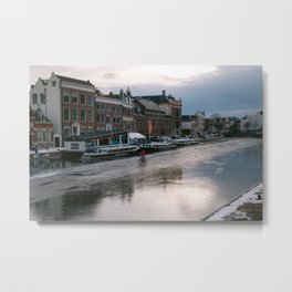 Dutch cyclist biking over a frozen canal in winter | Old historical city of Haarlem, Noord-Holland, Netherlands Metal Print