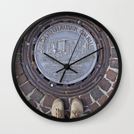 Man standing in front of a manhole Wall Clock