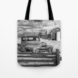 Black and White of Rusted International Harvester Pickup Truck behind wooden fence with Red Barn in Tote Bag