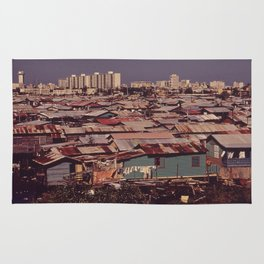 'MODERN BUILDINGS TOWER OVER THE SHANTIES CROWDED ALONG THE MARTIN PENA CANAL' Rug