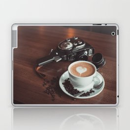 A cup of hot cappuccino placed on a table next to the old camera with lens and coffee beans Laptop & iPad Skin