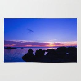 Blue sunset by rock beach Rug