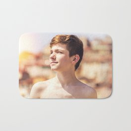 Boy relaxing on a beach in French Riviera Bath Mat