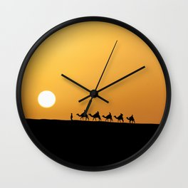 Caravan in the desert during sunset Wall Clock