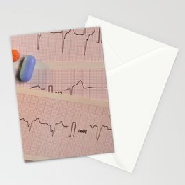 Colored pills on electrocardiogram strips Stationery Cards