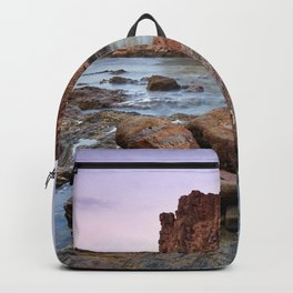 Submarine reef. Corralete beach at pink sunset. Backpack