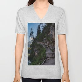 A path with a wooden fence climbs steeply beside the Braies lake Unisex V-Neck