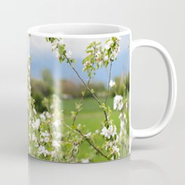 Flowering branches of an apple tree against a blue stormy sky Coffee Mug