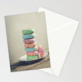 A stack of donuts on wooden table against the wall Stationery Cards