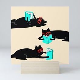 Book bag black cat reads stories Mini Art Print