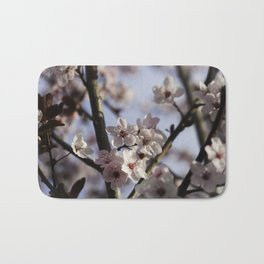 Pink Plum Tree Blossoms against a Blue Sky Bath Mat