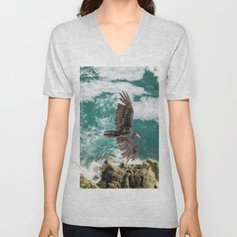 AERIAL PHOTOGRAPHY OF VULTURE FLYING ON TOP OF ROCK FORMATION BESIDE SEA AT DAYTIME Unisex V-Neck