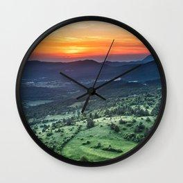 Beautiful sunset behind green fields Wall Clock