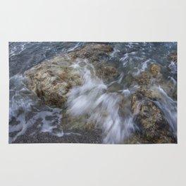 Crashing wave in a rocky beach Rug