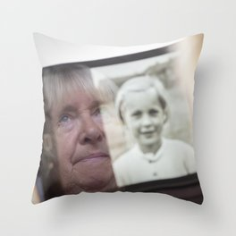 Senior woman looking an image of herself as a child on a tablet computer Throw Pillow