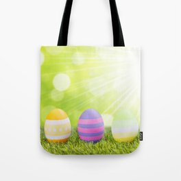 Decorated Easter eggs in the grass with a green background Tote Bag