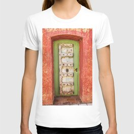 White and green wooden door with red wall in a typical village in Provence France T-shirt