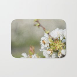 Bee laid on white flowers of a cherry tree Bath Mat