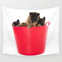 puppies Wall Tapestries featuring Three puppies in red laundry basket by AvHeertum